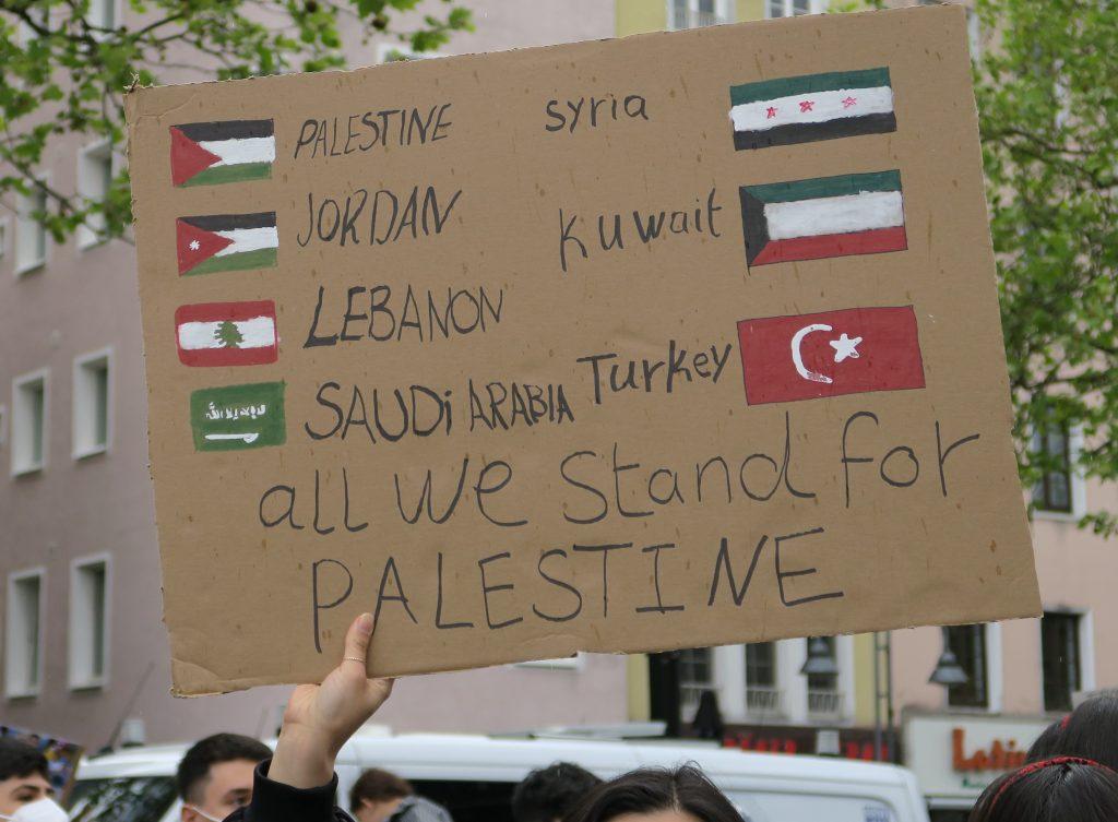 """Schild mit Flaggen arabischer Staaten und der Aufschrift """"All we stand for Palestine"""""""