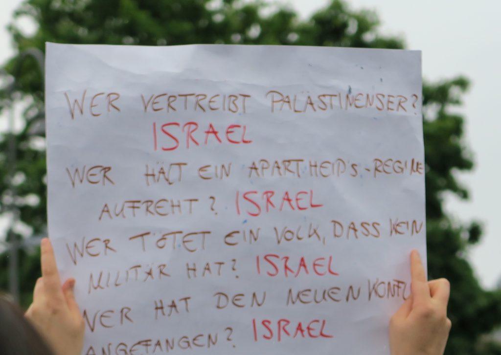 """Plakat, auf dem Israel für alles böse verantwortlich gemacht wird. Aussage: """"Wer vertreibt Palästinenser? Israel. Wer hält ein Apartheids-Regime aufrecht? Israel, usw."""