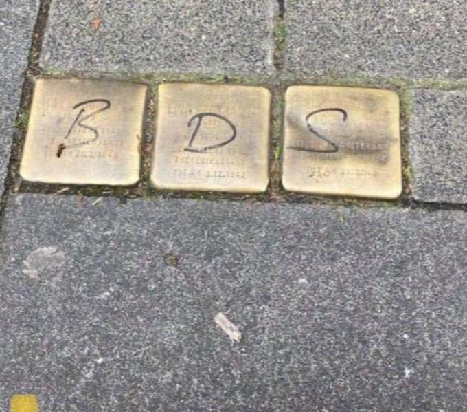 Drei geschändete Stolpersteine mit den Buchstaben BDS