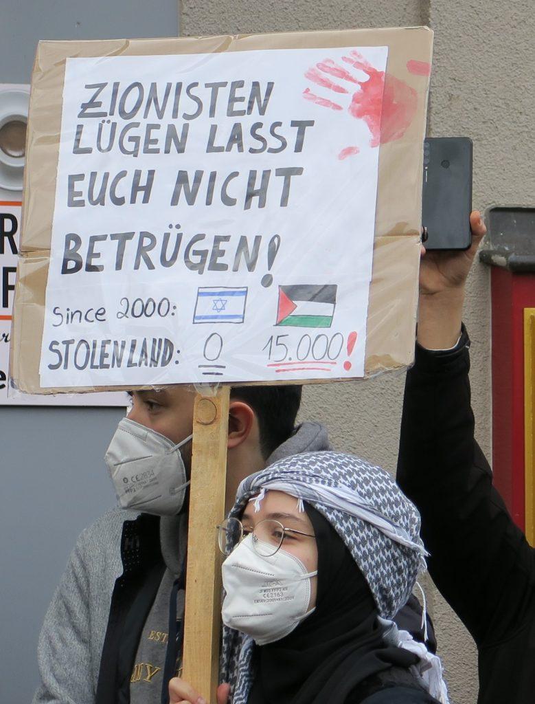 """Demonstrations-Teilnehmerin hält Schild mit Aufschift """"Zionisten lügen lasst euch nicht betrügen"""""""