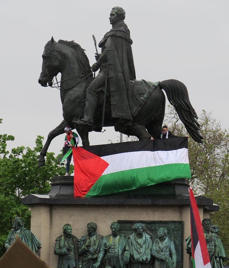 Zwei Demonstranten hissen Palästina-Flagge auf dem Reiterdenkmal am Heumarkt